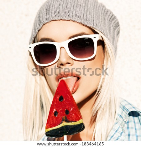 Portrait of sexy blond girl in white sunglasses and beanie hat licking watermelon lollipop with tongue - stock photo