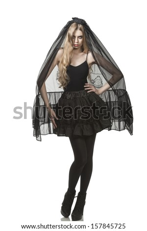 portrait of sexy blonde girl with dark style and bizarre make-up in Halloween day, she wearing funeral long black veil, gothic skirt and sexy shoes    - stock photo
