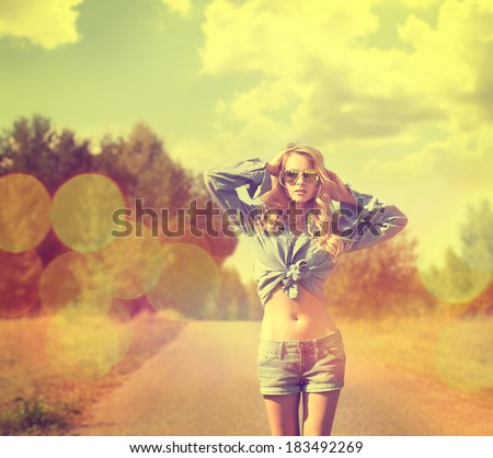 Portrait of Sexy Blonde Woman with Hands behind her Head Walking on Country Road. Toned Photo with Bokeh. Hipster Style. - stock photo