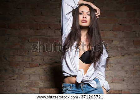 Portrait of sexy brunette posing in black bra and white shirt - stock photo