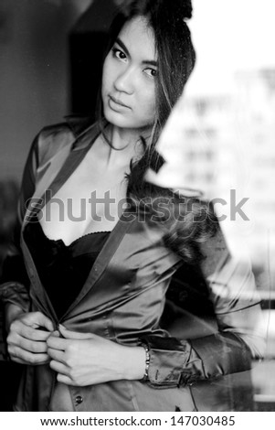 Portrait of sexy brunette woman behind the window, black and white photo - stock photo