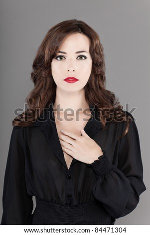 Portrait of sexy Caucasian middle aged woman with beautiful green eyes and red lips isolated on gray background - stock photo