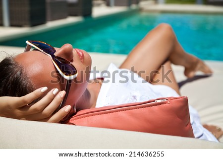 Portrait of sexy cheerful woman holding hand behind head, relaxing at the luxury poolside. Girl at travel spa resort pool. Summer luxury vacation. (focus on woman face) - stock photo