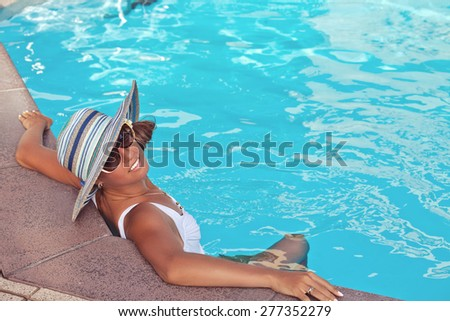Portrait of sexy cheerful woman in straw hat, relaxing at the luxury poolside. Girl at travel spa resort pool. Summer luxury vacation. - stock photo
