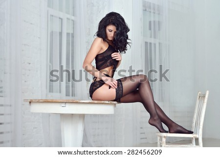 Portrait of sexy fashion model girl indoors. Beautiful lady in elegant black panties and stockings. Beauty brunette woman with attractive buttocks in lace lingerie. Female ass in underwear. Naked body - stock photo