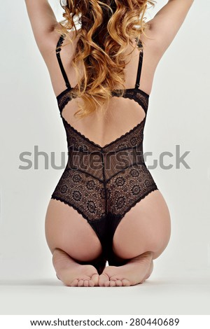 Portrait of sexy fashion model girl isolated on white background. Beautiful lady in elegant black bodysuit. Beauty brunette woman with attractive buttocks in lace lingerie. Female ass in underwear - stock photo