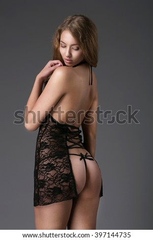 Portrait of sexy fashion model girl on grey. Beautiful lady in elegant black panties and stockings. Beauty brunette woman with attractive buttocks in lace lingerie. Female ass in underwear. Naked body - stock photo