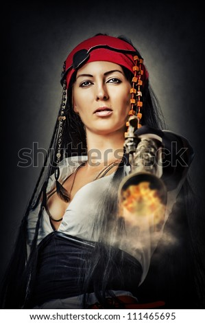 Portrait of sexy female pirate shooting from an old pistol - stock photo