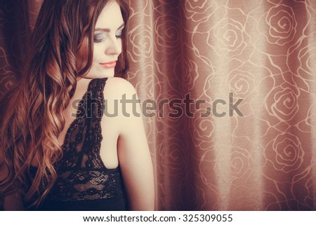 Portrait of sexy gorgeous woman by curtain. Attractive sensual young girl with long hair in lingerie. Female fashion.