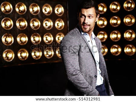 portrait of sexy handsome fashion male model man dressed in elegant suit on black studio lights background