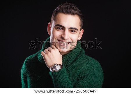 Portrait of sexy man in green sweater over dark background wearing a chronograph wrist watch - stock photo