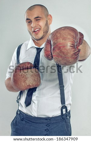 Portrait of sexy man posing in studio in boxing gloves - stock photo