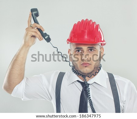 Portrait of sexy man posing in studio in red helmet with phone - stock photo