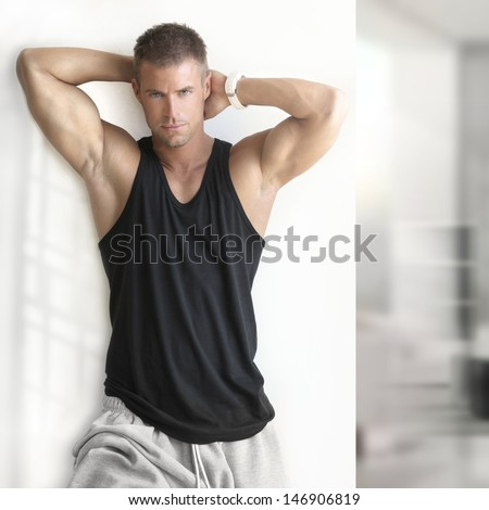 Portrait of sexy muscle man posing in modern studio - stock photo