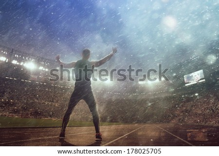 Portrait of sexy muscle man posing on stadium in epic rain