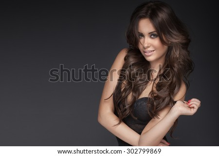 Portrait of sexy naked woman with big brown eyes and long curly hair. Studio shot. - stock photo