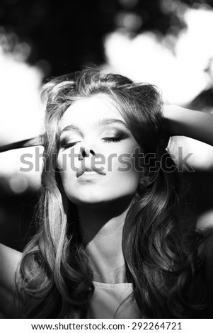 Portrait of sexy sensible young blonde lady with bright makeup touching curly hair outdoor on natural background black and white, vertical background - stock photo