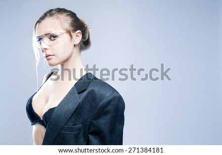 Portrait of Sexy Sensual Caucasian Blond Model Dressed in Grey Modern Suite and Posing in Transparent Glasses Against Gray Background. Horizontal Image Concept - stock photo