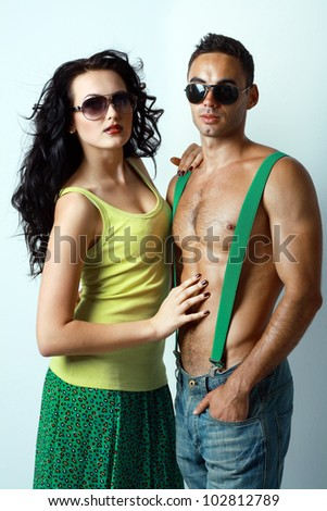 Portrait of sexy stylish young couple macho man and woman both wearing sunglasses - stock photo