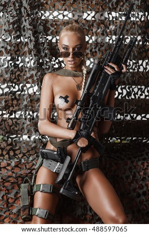 portrait of sexy topless blonde in sunglasses posing with rifle against camouflage net