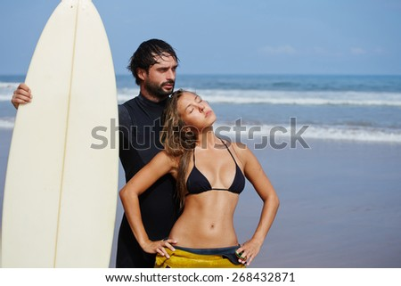 Portrait of sexy woman in bikini enjoying the sun standing next to male surfer, handsome brunette surfer holding copy space surf board standing on the beach with beautiful waves background - stock photo