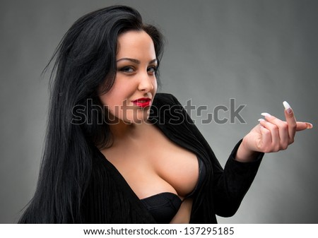 Portrait of sexy woman in black dress on a gray background - stock photo