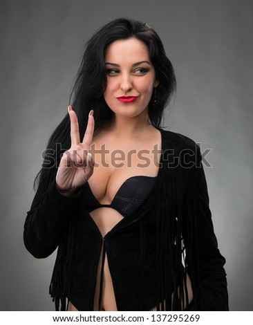 Portrait of sexy woman in black dress on a gray background