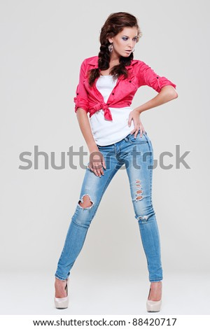 portrait of sexy woman in blue jeans and red shirt posing against grey background - stock photo