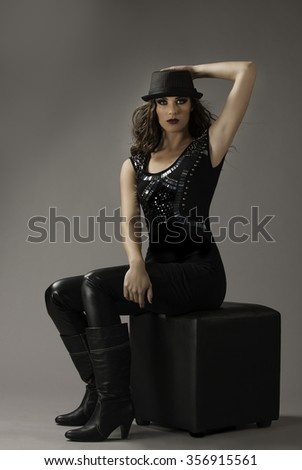 Portrait of sexy woman in rocker chick outfit with sparkling beads, leggings, boots and hat, wearing her dark hair in a wild loose style, seated on a black chair. - stock photo