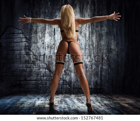 Portrait of sexy woman in underwear on a dark wall - stock photo