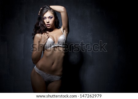 Portrait of sexy woman in white underwear on a dark wall
