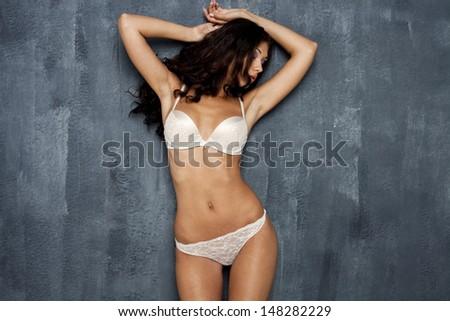 Portrait of sexy woman in white underwear on a dark wall - stock photo