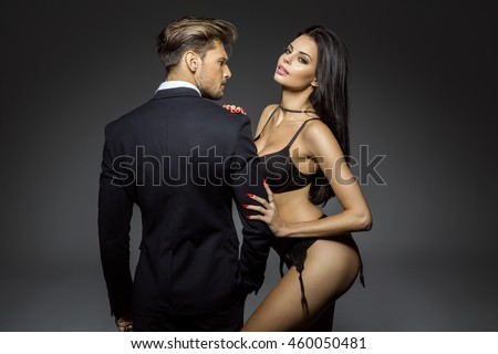 Portrait of sexy woman wear lingerie and hugging handsome man in black suit