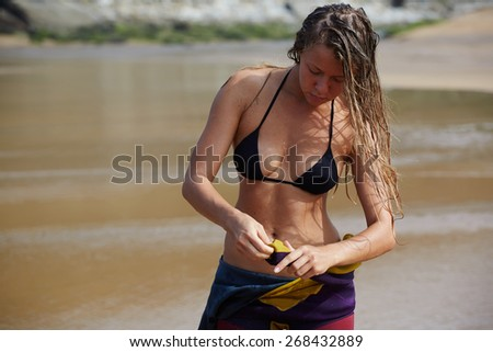 Portrait of sexy woman with long wet hair getting ready to surfing at sunny day, attractive model in bikini preparing for surf session - stock photo