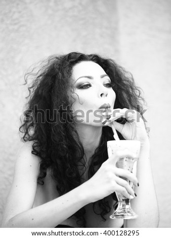 Portrait of sexy young brunette lady with curly hair bright makeup and manicure drinking cocktail from straw on blurred background, black and white - stock photo