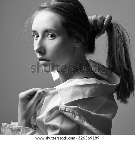 portrait of sexy young Caucasian blonde with blue eyes and provocative look isolated on grey background black and white