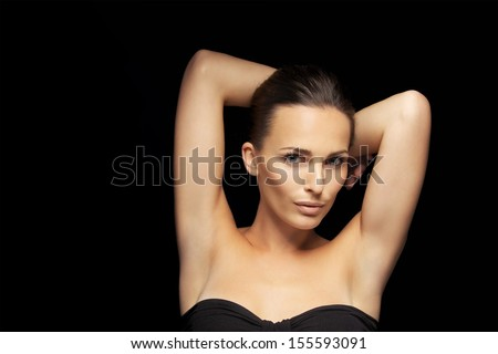 Portrait of sexy young lady posing with her hands behind head.  Sensual female model posing on black background - stock photo