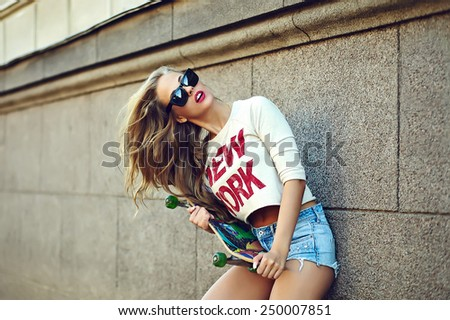 portrait of sexy young stylish smiling woman girl model in bright modern cloth in glasses outdoors in the street in jean shorts with skateboard - stock photo