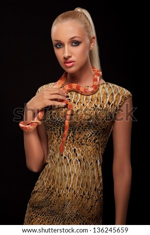 portrait of sexy young woman holding orange snake against black background