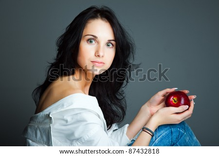 Portrait of sexy young woman with fresh red apple on gray background - stock photo