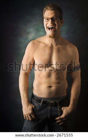 Portrait of shirtless adult Caucasian man on studio background laughing. - stock photo