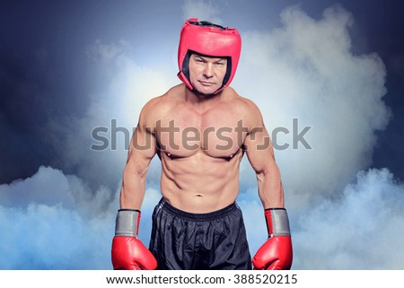 Portrait of shirtless man with boxing headgear and gloves against cloudy sky - stock photo
