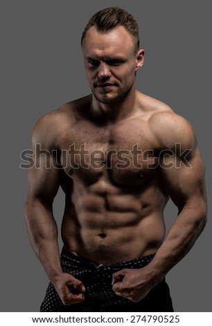 Portrait of shirtless muscular guy isolated on grey background