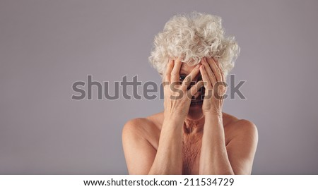 Portrait of shirtless old lady covering her face and looking through fingers against grey background. Happy senior woman on grey background. - stock photo
