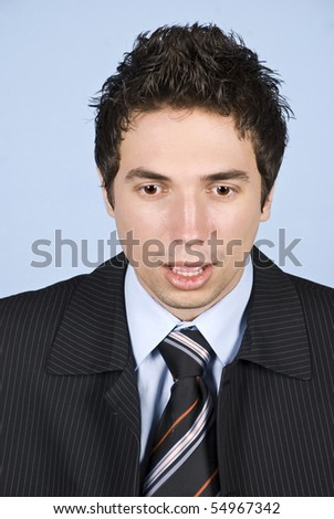 Portrait of shocked business man looking down in front of blue background - stock photo
