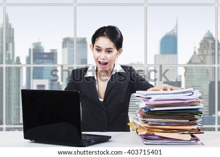 Portrait of shocked businesswoman doing her job with a laptop and a pile of paperwork in the office - stock photo