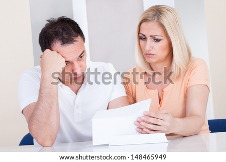 Portrait of shocked couple looking at bill - stock photo