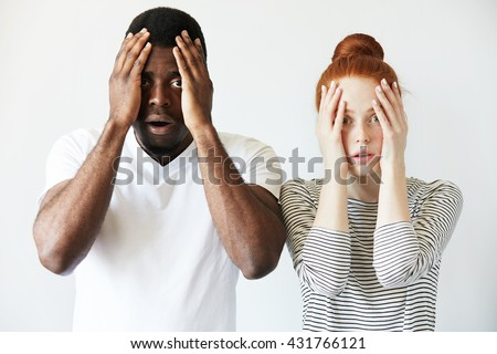 Portrait of shocked interracial couple: African man and redhead Caucasian woman standing together against white wall, covering face, looking at the camera with scared and disappointed expression - stock photo