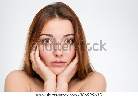 Portrait of shocked pretty young woman touching her face over white background - stock photo