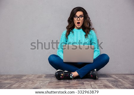 Portrait of shocked woman sitting on the floor with laptop and looking at camera on gray background - stock photo